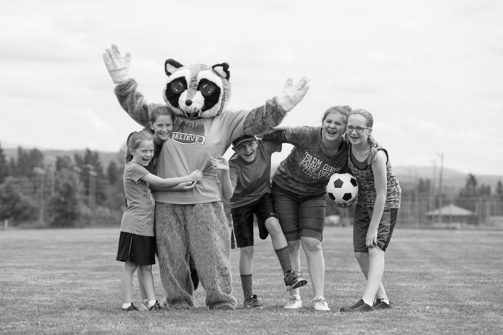 raccoon mascot posing with kid soccer players