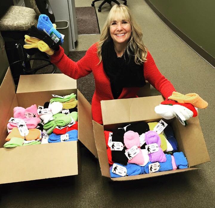 woman kneeled down in front of boxes of fuzzy socks holding some up