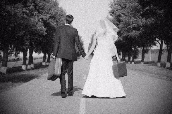 grainy photo of a just married couple walking down road with suitcases in hands
