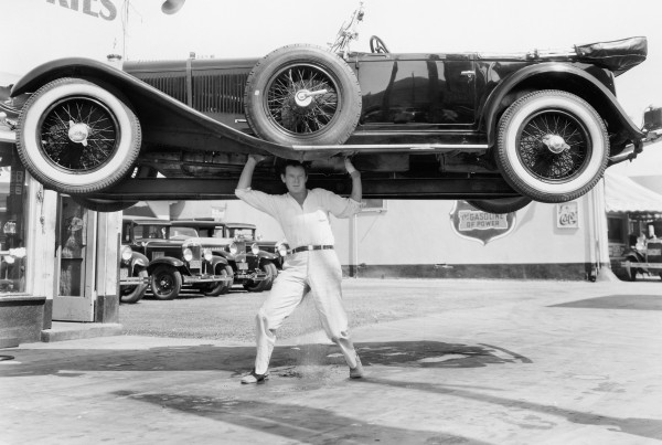 old photo of a man lifting a car over his head