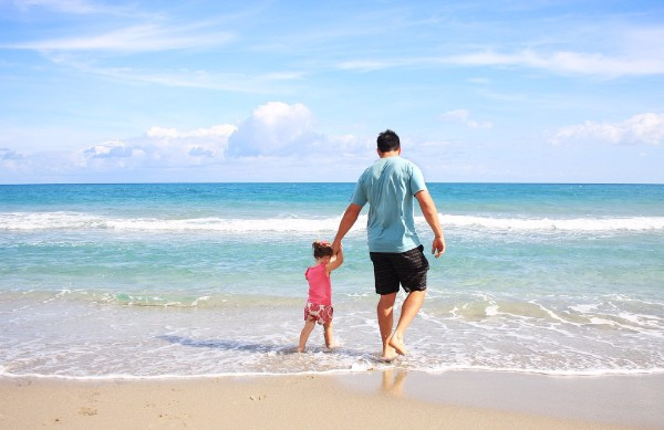 father and daughter holding hands walking on beach