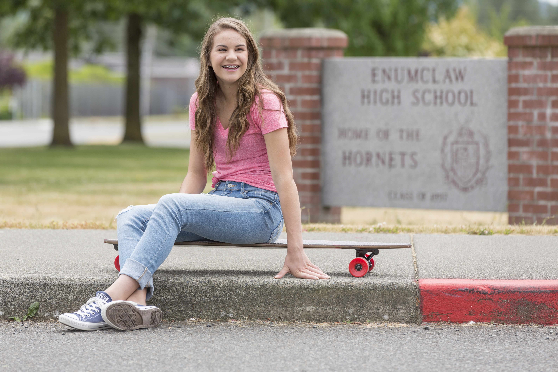 teenage girl outside a school on a skateboard