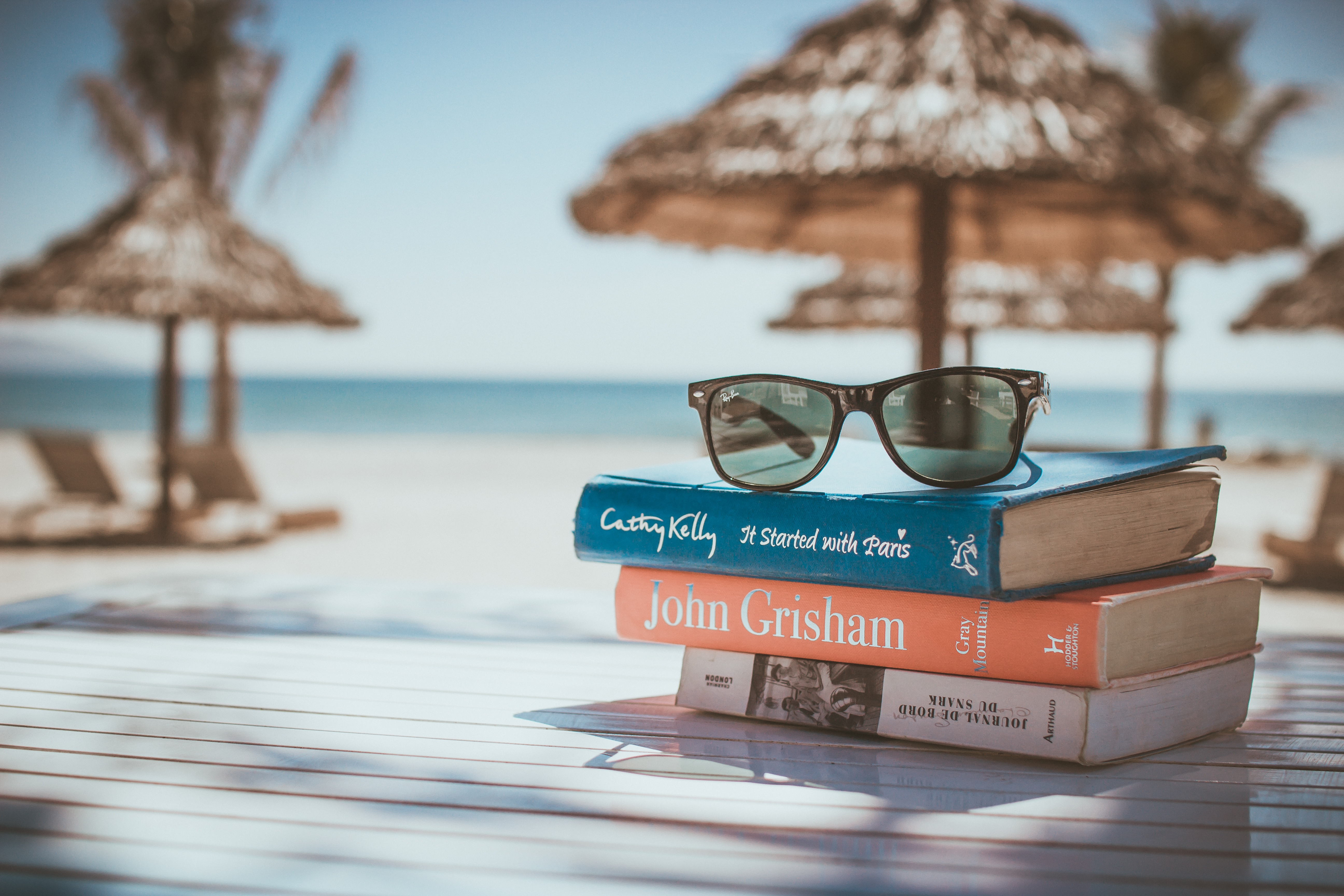 stack of books with sunglasses on top on a beach