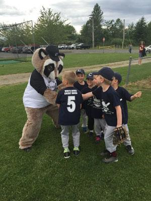 Raccoon mascot with a boys baseball team