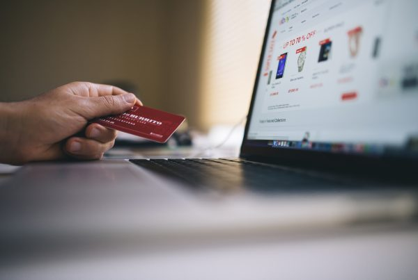 person holding a credit card while working on a laptop