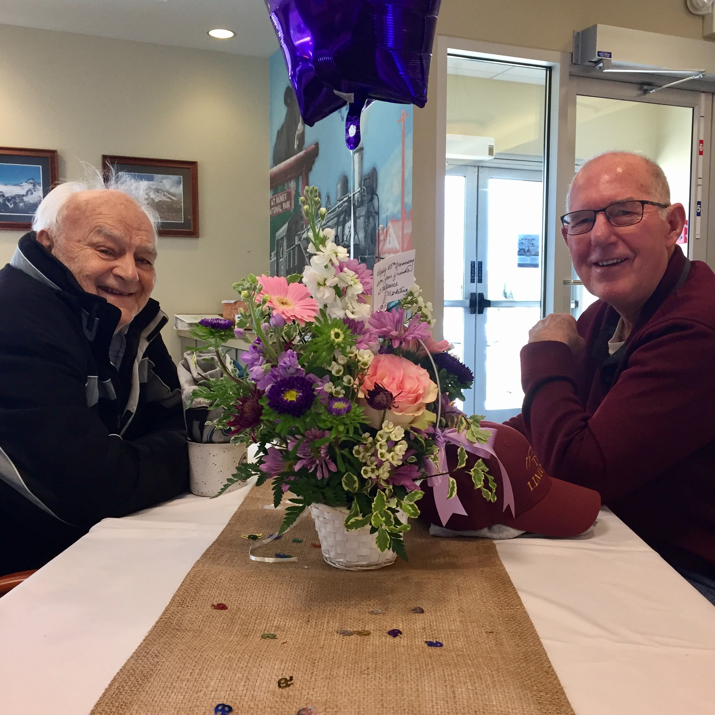 men sitting at a table with flowers and balloons