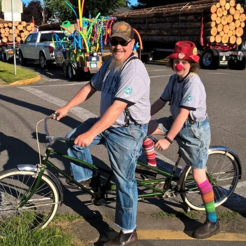 two people riding a tandem bike dressed as clowns
