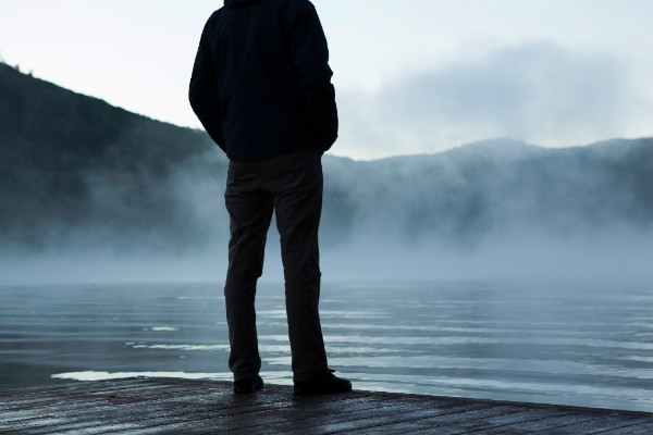 person standing on edge of foggy lake