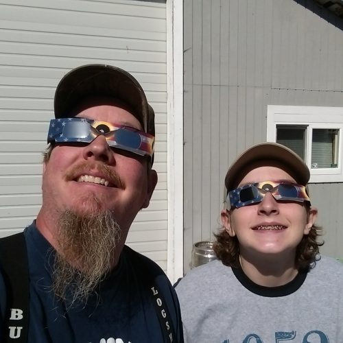 father and son looking at the Eclipse with special glasses on