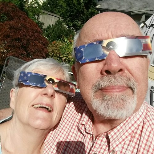 husband and wife looking at the Eclipse with special glasses on