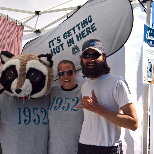 Raccoon mascot posing outside with people