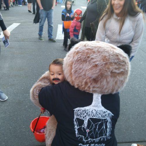 Raccoon mascot hugging a little boy on Halloween