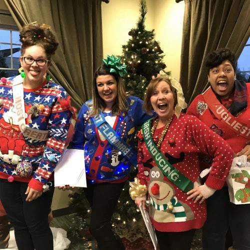 women posing wearing ugly holiday sweaters