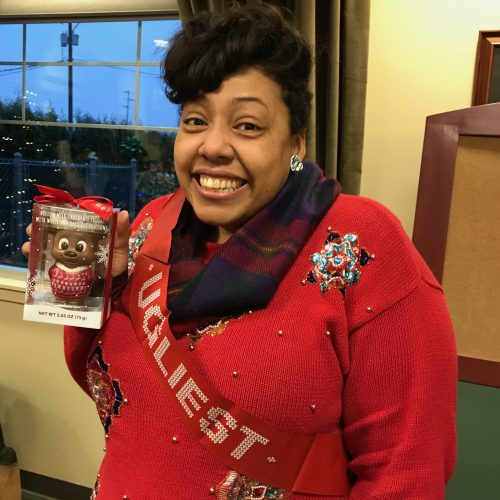 woman posing wearing ugly holiday sweater and holding a chocolate figurine