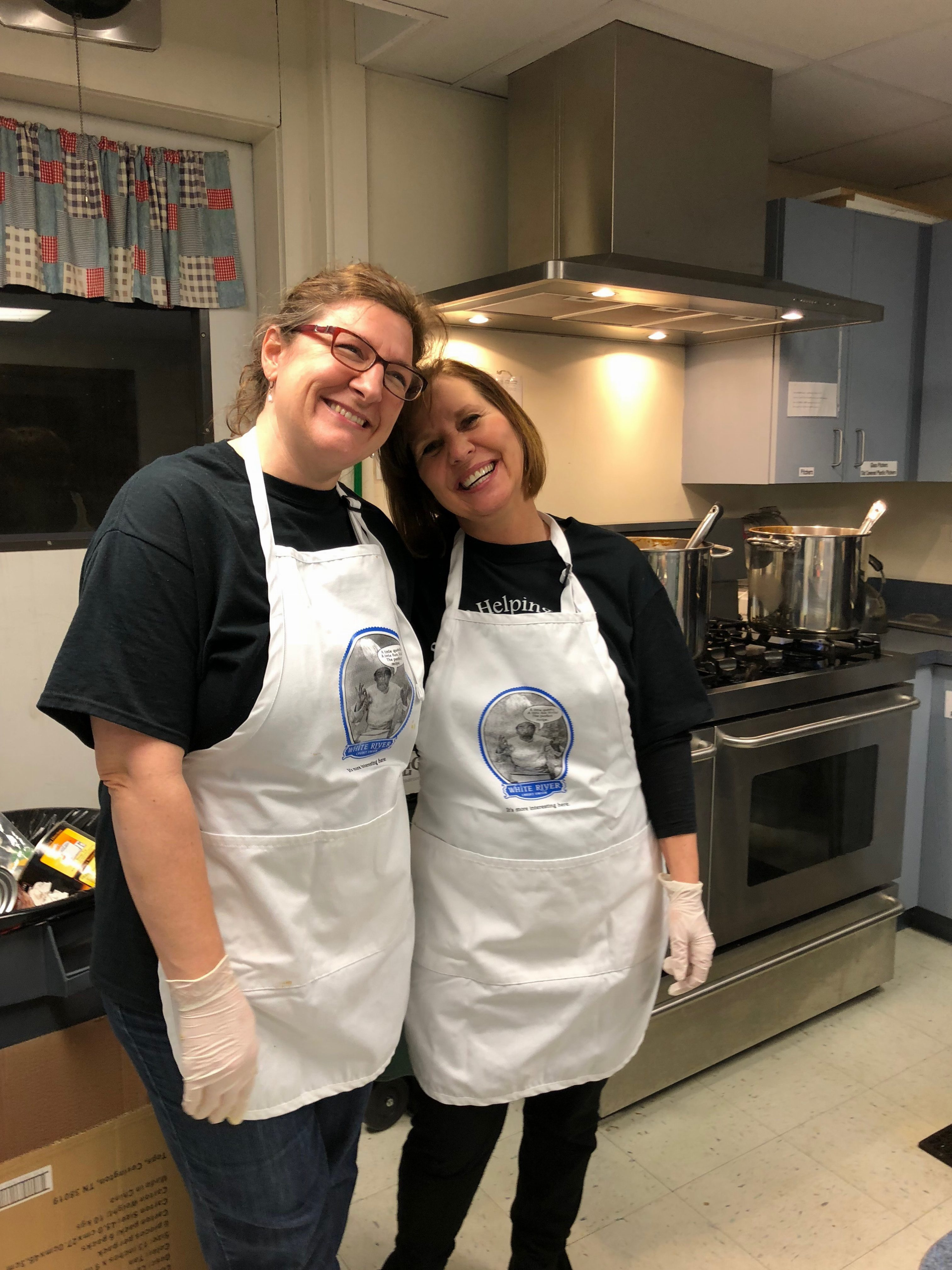 two women in aprons in a kitchen