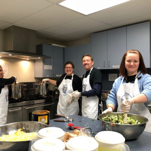four people in aprons cooking in a kitchen
