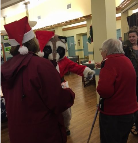 Raccoon Santa dressed person greeting elderly people in a Nursing Home