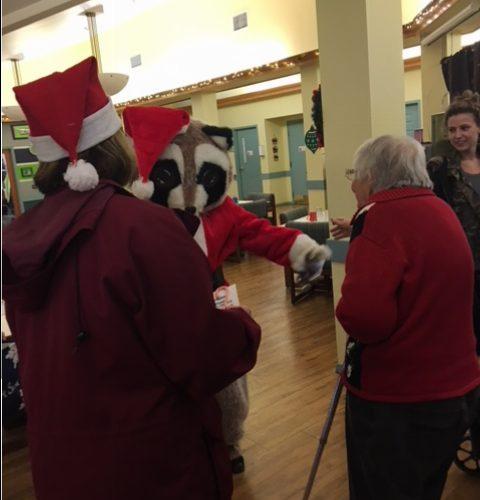 Raccoon Santa dressed person greeting elderly people in a Nursing Home