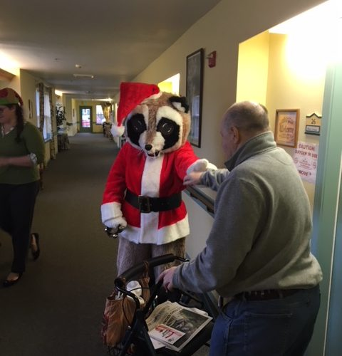Raccoon Santa dressed person walking down a hallway