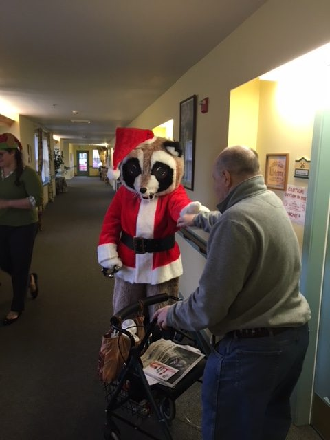 Raccoon Santa dressed person walking down a hallway