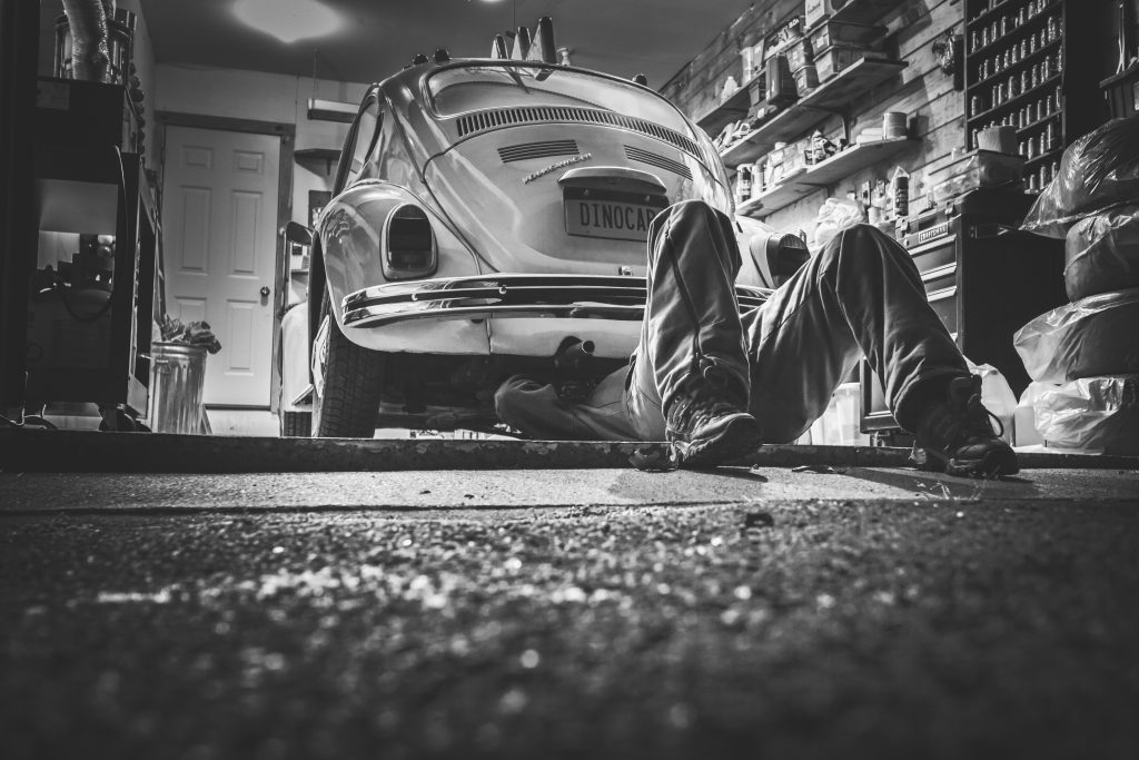 black and white image of mechanic working under a Volkswagon Bug