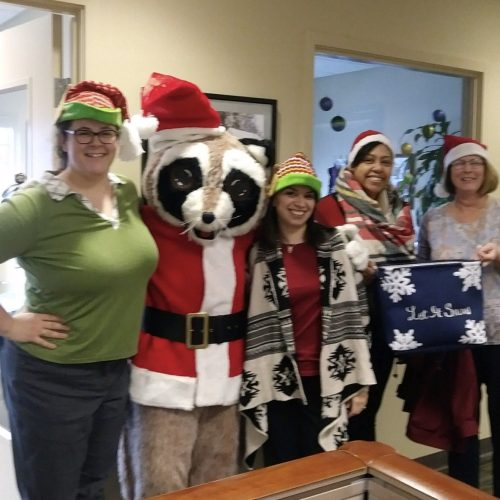 group photo of people dressed in Holiday themed attire and a person in a Raccoon Santa constume