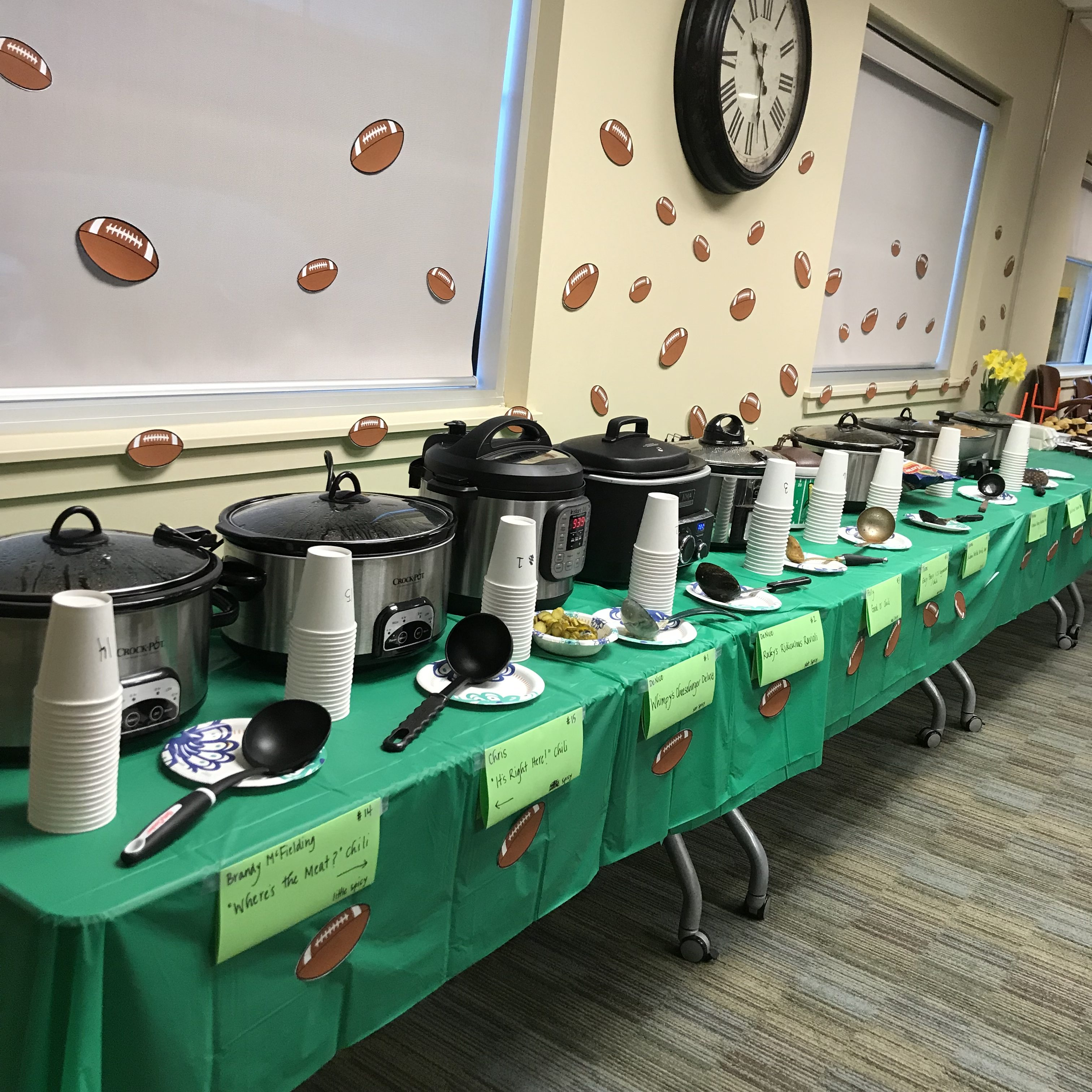 crock pots lined up with on a table during a chili cookoff