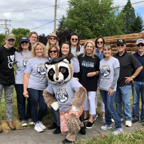 WRCU staff standing with Rocky the Raccoon in the middle