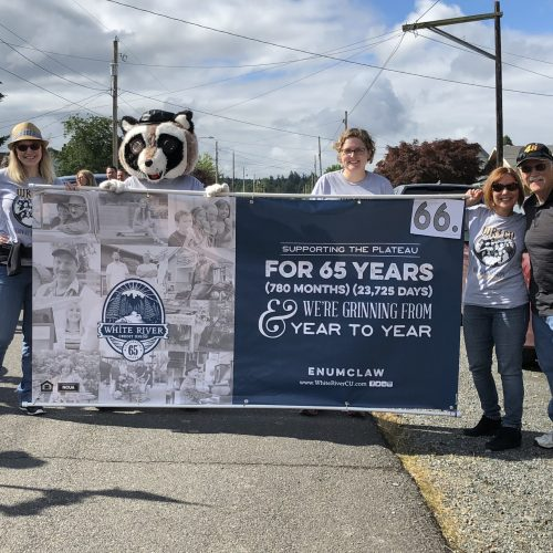"WRCU staff and Rocky the Raccoon holding a banner that says, ""supporting the plateau for 65 years, we're grinning from year to year."""