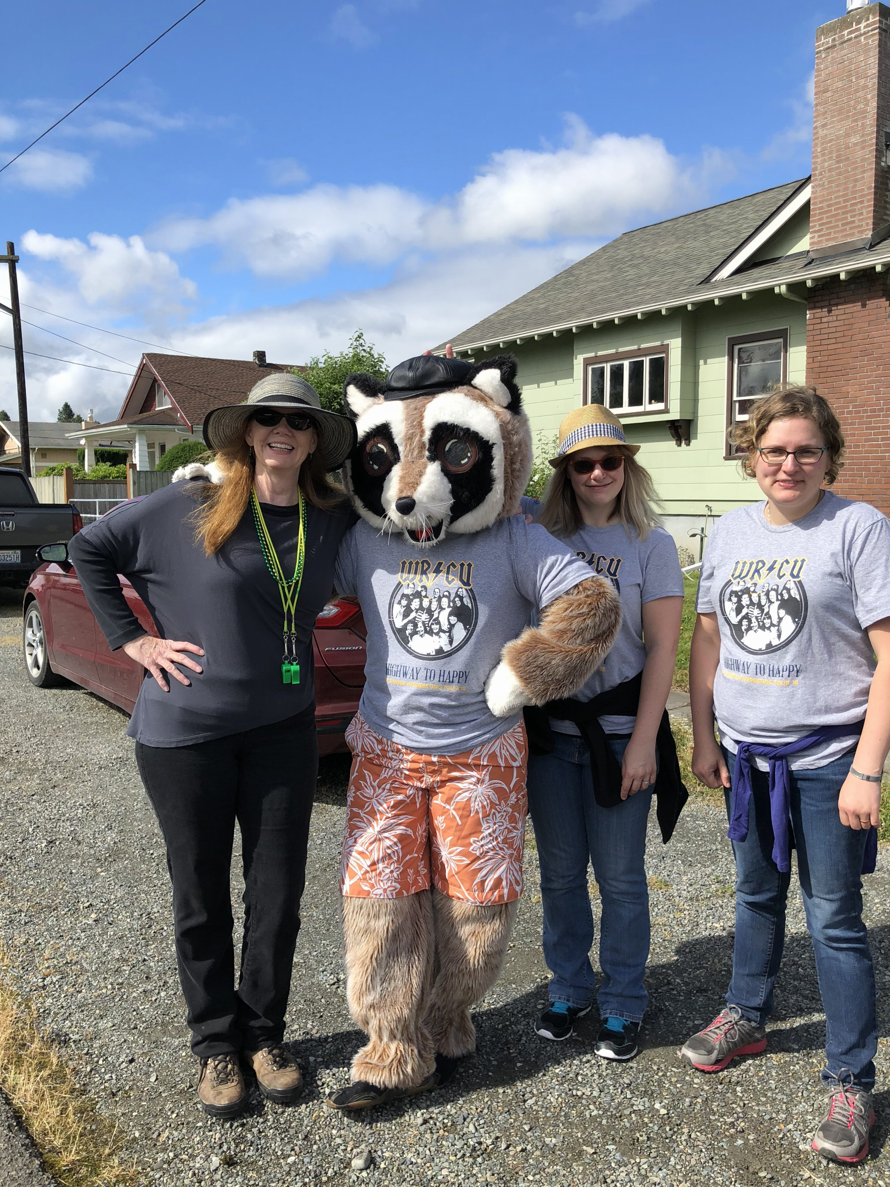 Rocky the Raccoon posing with three event attendees who are wearing WRCU t-shirts
