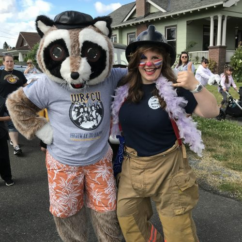 Rocky the Raccoon posing with a woman who is throwing a shaka and wearing firefighter costume