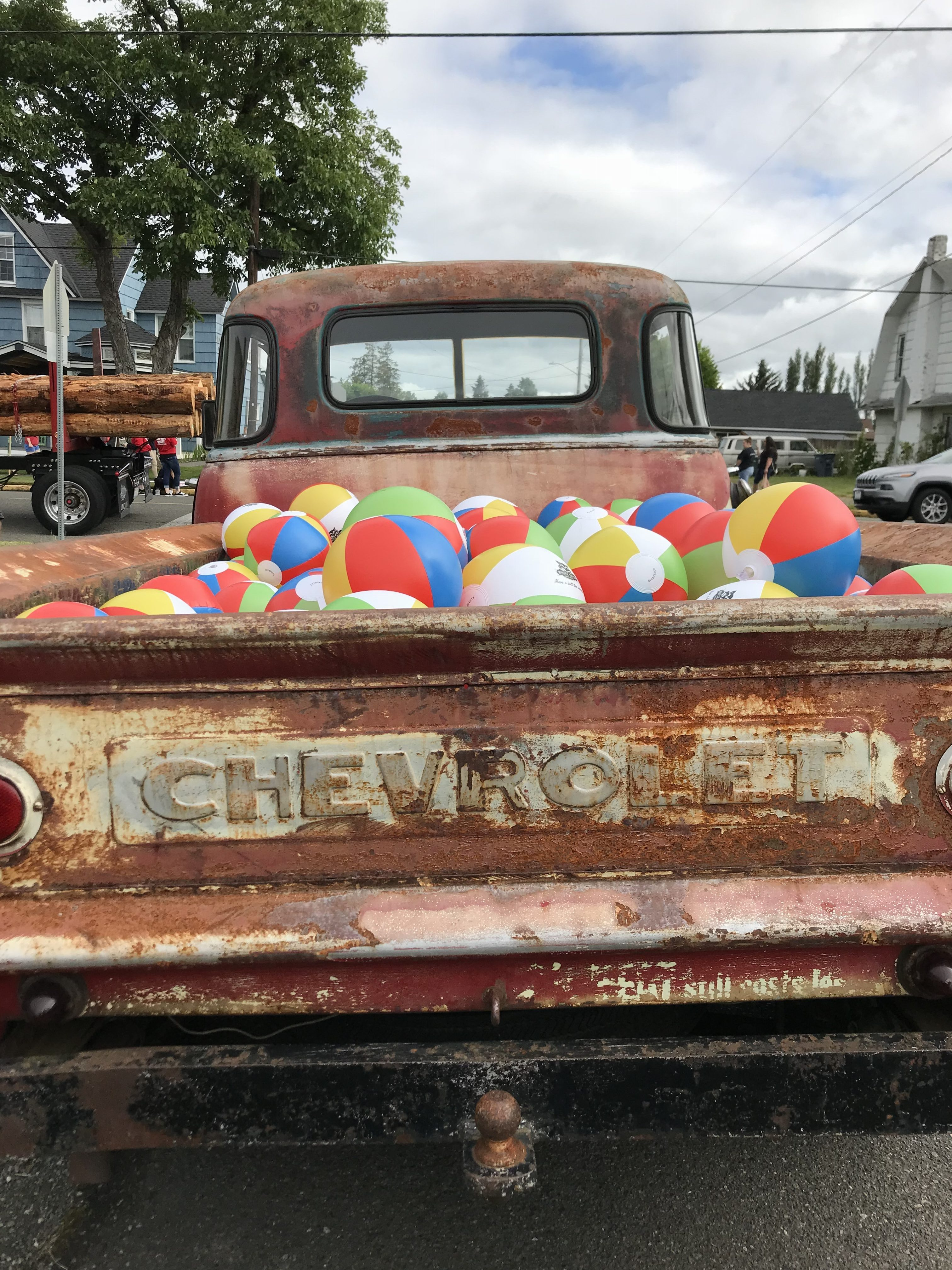 Lots of colorful beach balls in the back of an old pick up Chevy truck