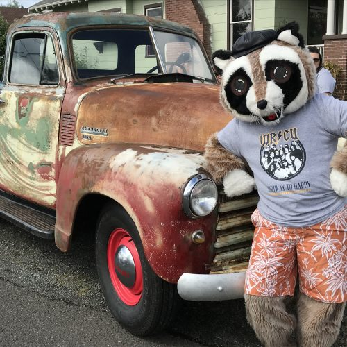 Rocky the Raccoon leaning against the old pickup truck