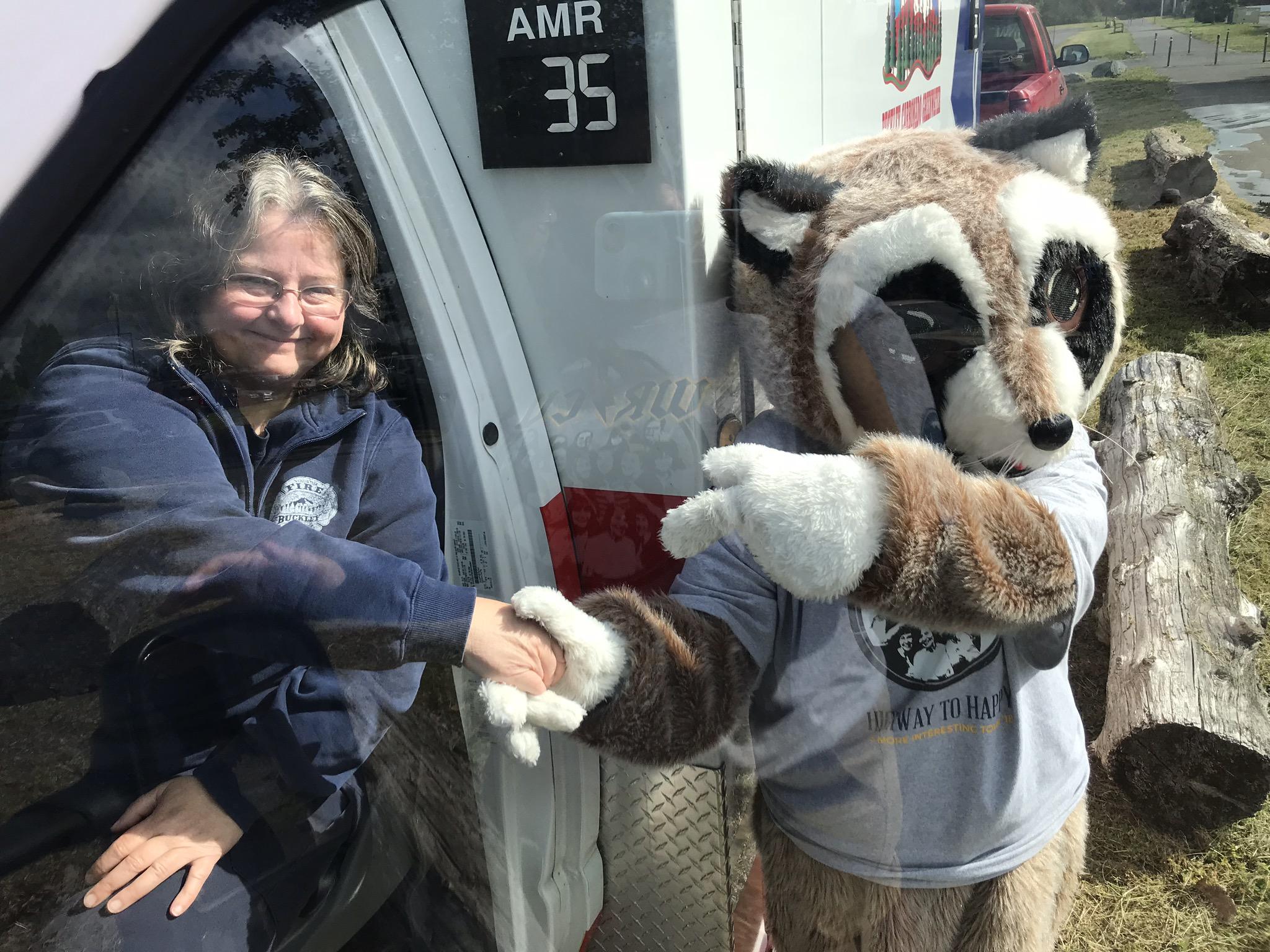 Rocky Raccoon shaking lady's hand