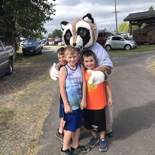 Rocky Raccoon standing with little boys