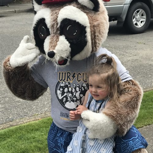 Rocky Raccoon hugging little girl