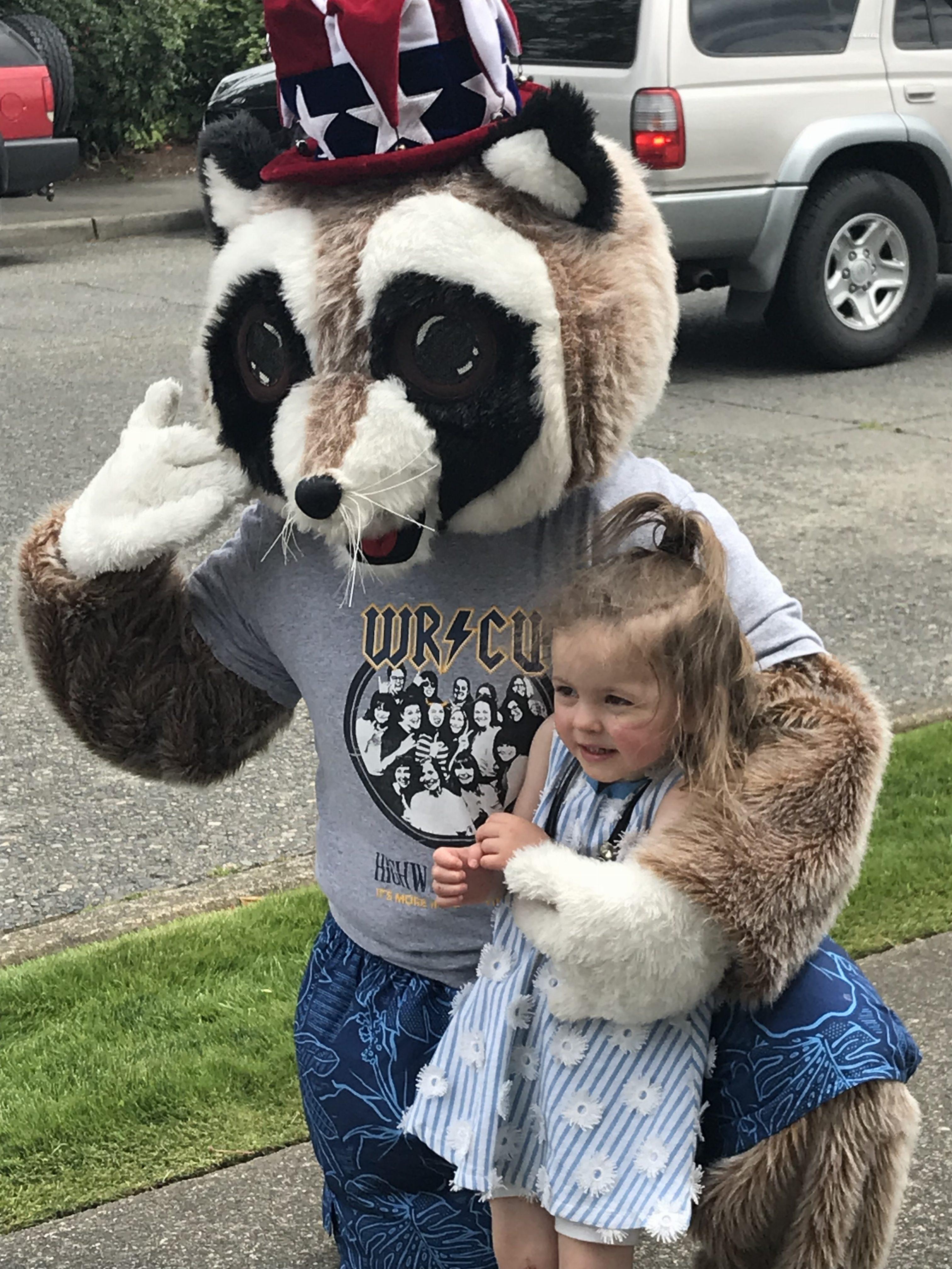 Rocky Raccoon hugging little girl