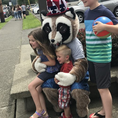 Kids sitting on Rocky Raccoons lap