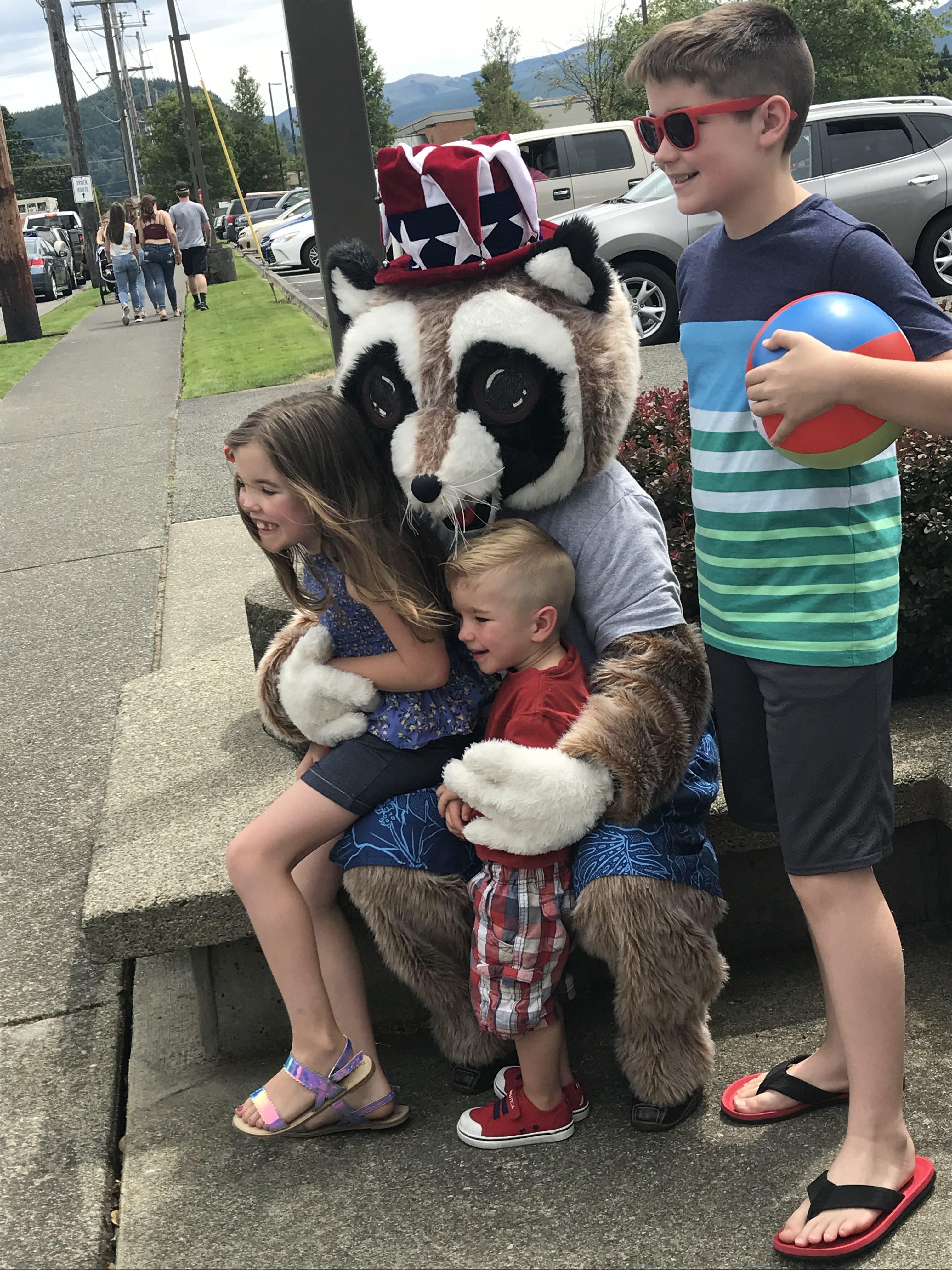 Kids sitting on Rocky Raccoons lap