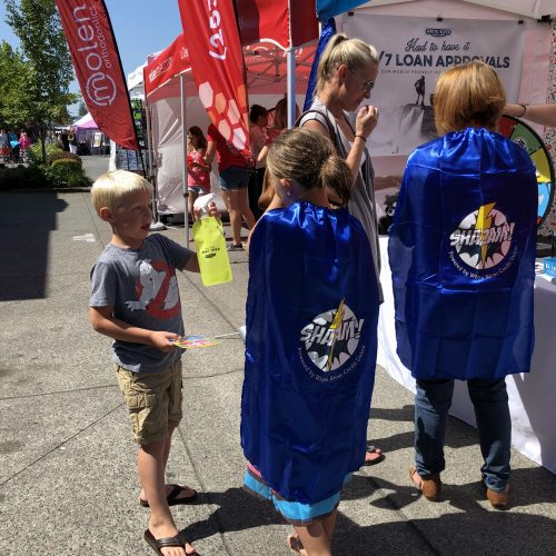 Kids with WRCU capes on at the Street Fair booth