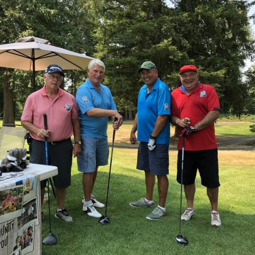 Male golfers standing near WRCU booth