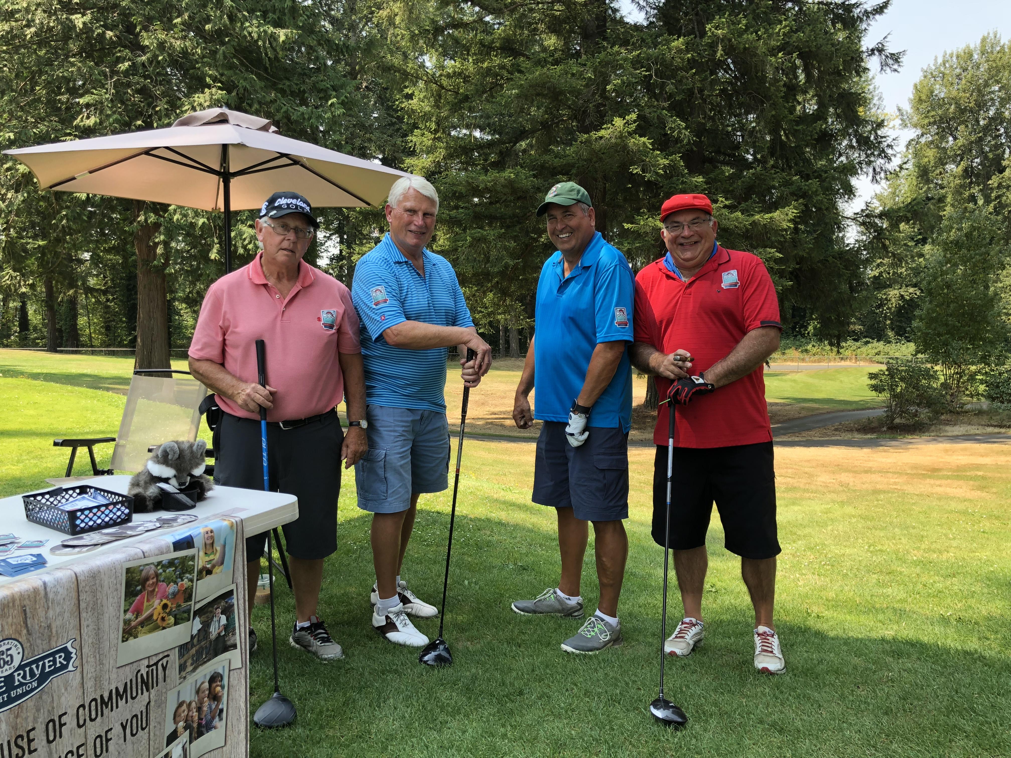 Male golfers standing near WRCU booth