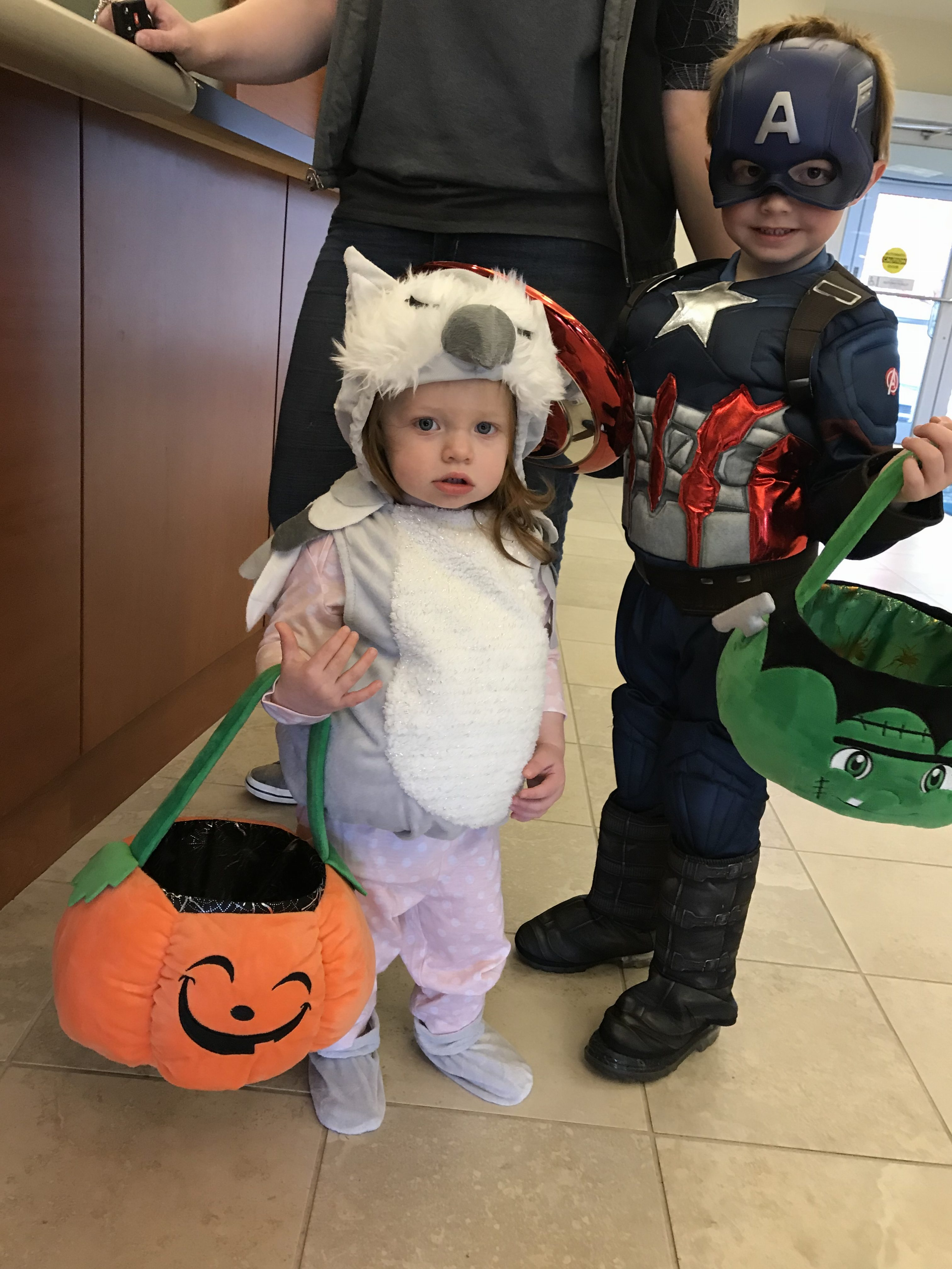 Kids dressed in costumes with Halloween buckets