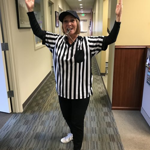 Woman in ref shirt with arms raised