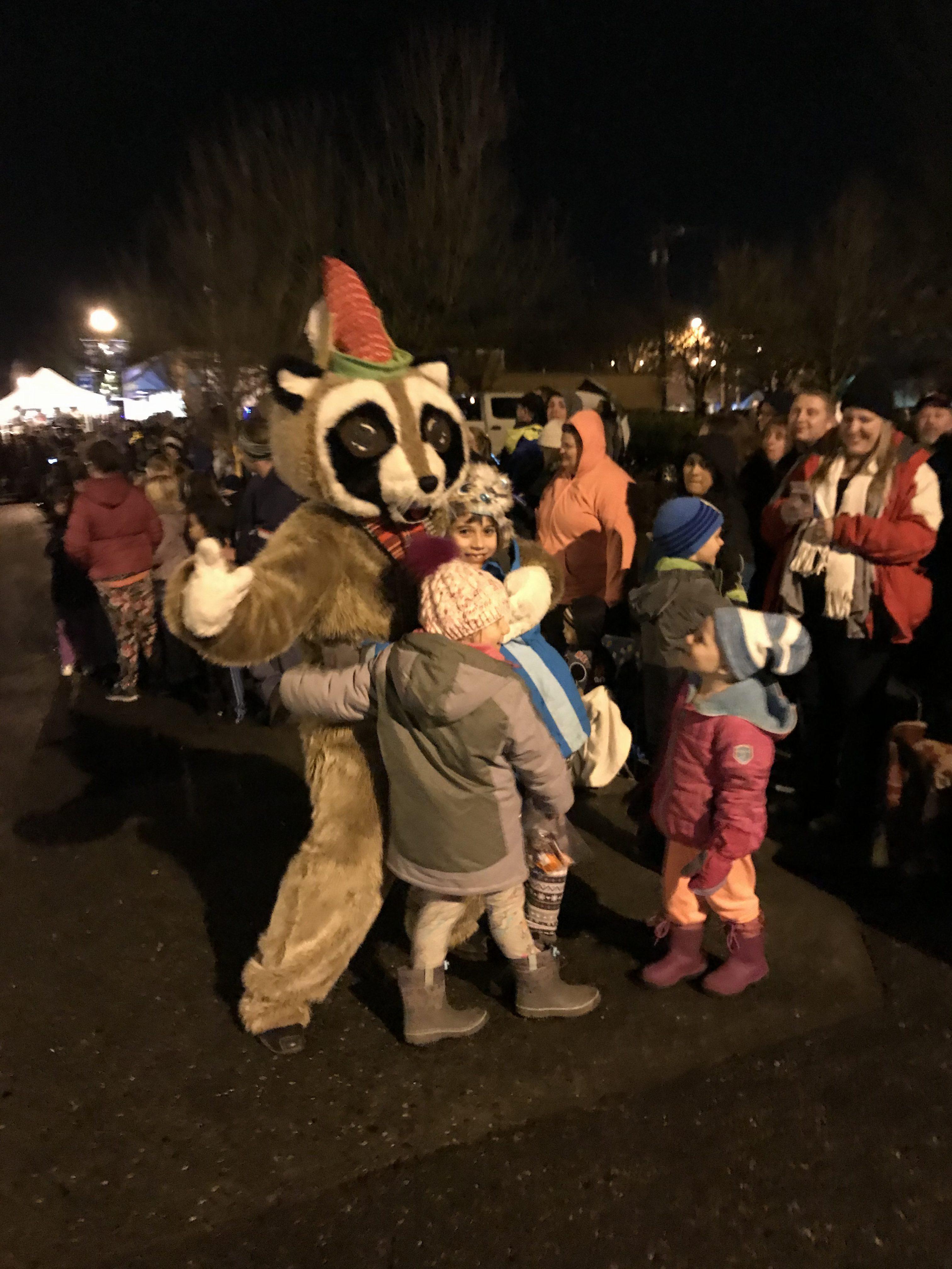Rocky Raccoon hugging group of kids