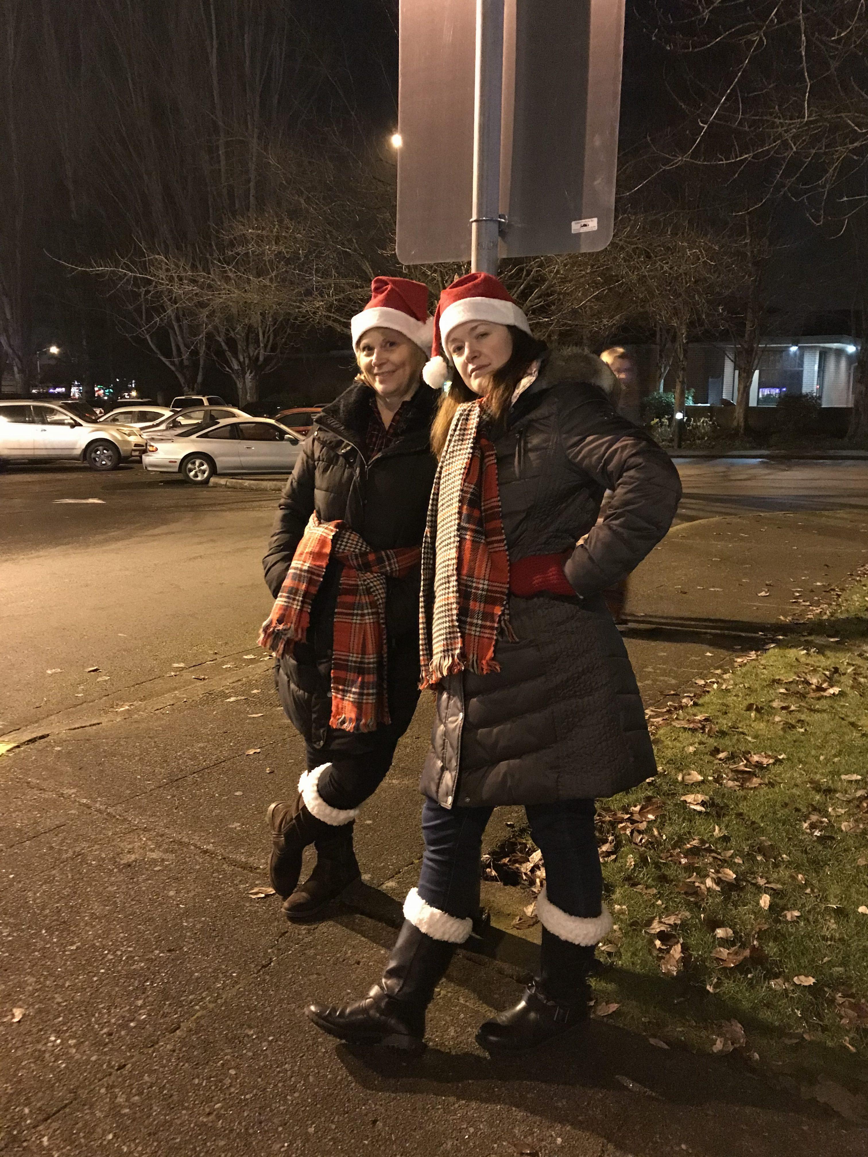 Two ladies in warm coats standing on sidewalk