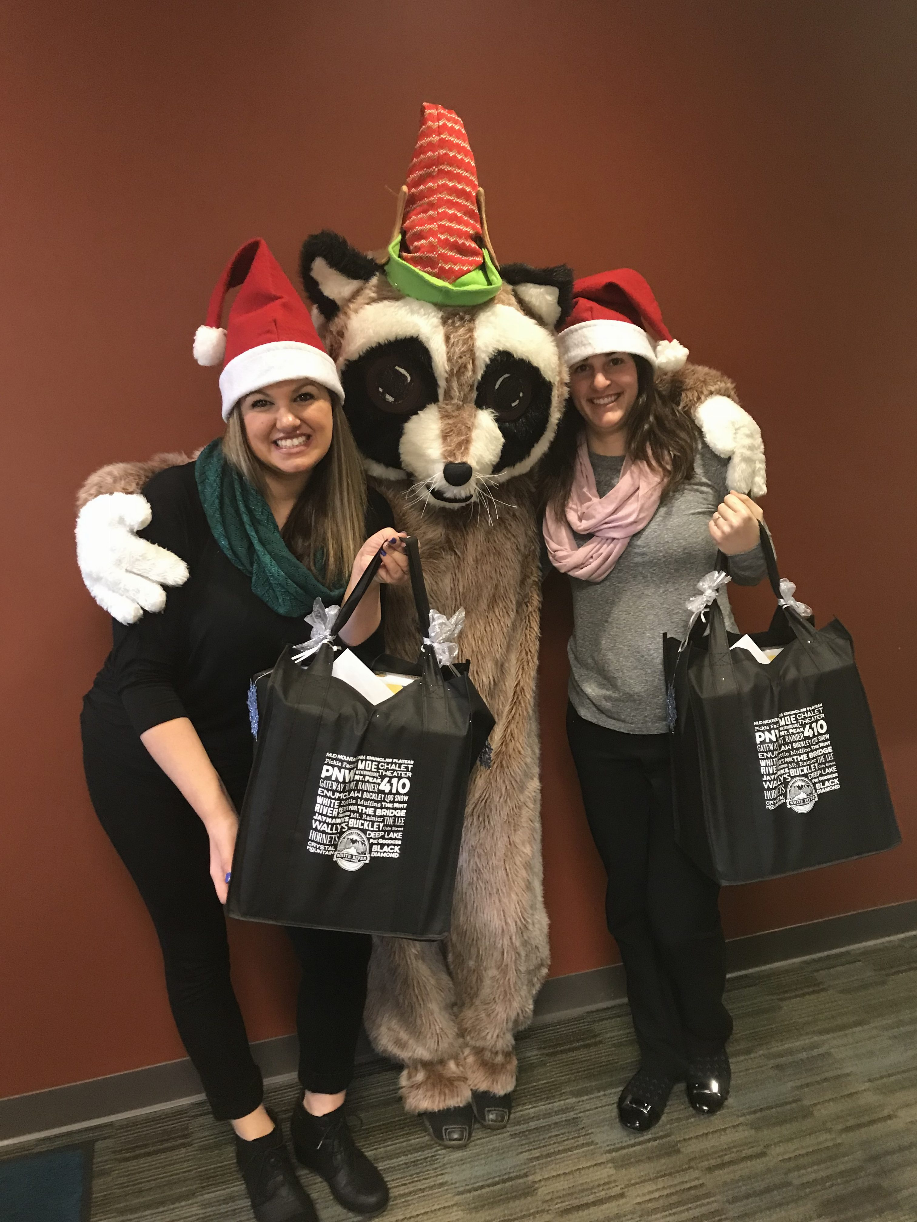 Rocky and two WRCU staff holding gifts