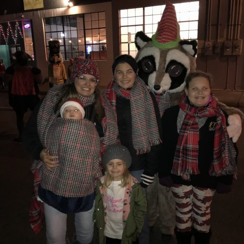Rocky Raccoon standing with kids and adults at a parade