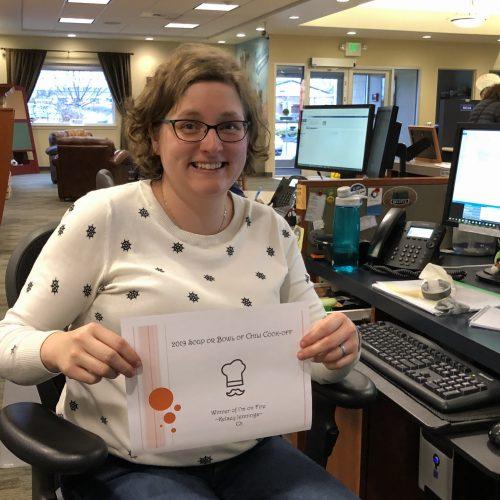 WRCU employee holding winner certificate