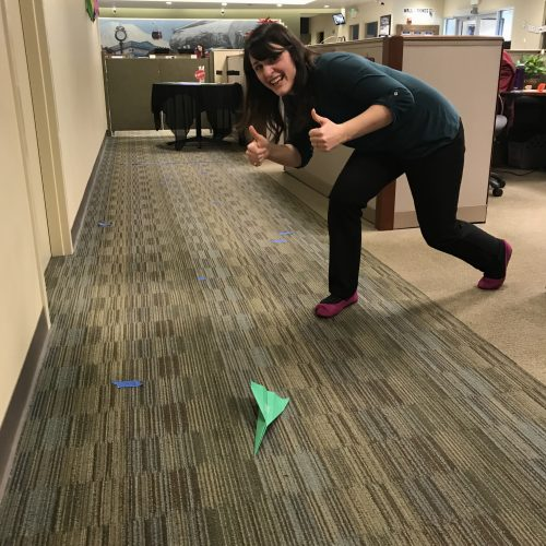 WRCU staff member throwing paper airplane